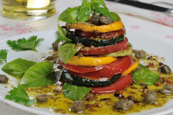 Appetizer of zucchini with tomato, pesto and capers